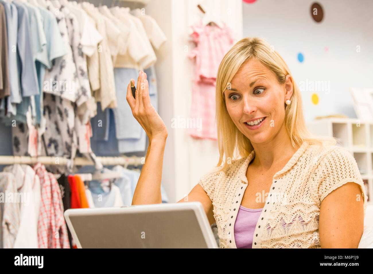 A woman working on a computer in her childrens clothing store looking as if she just realized something. - Stock Image