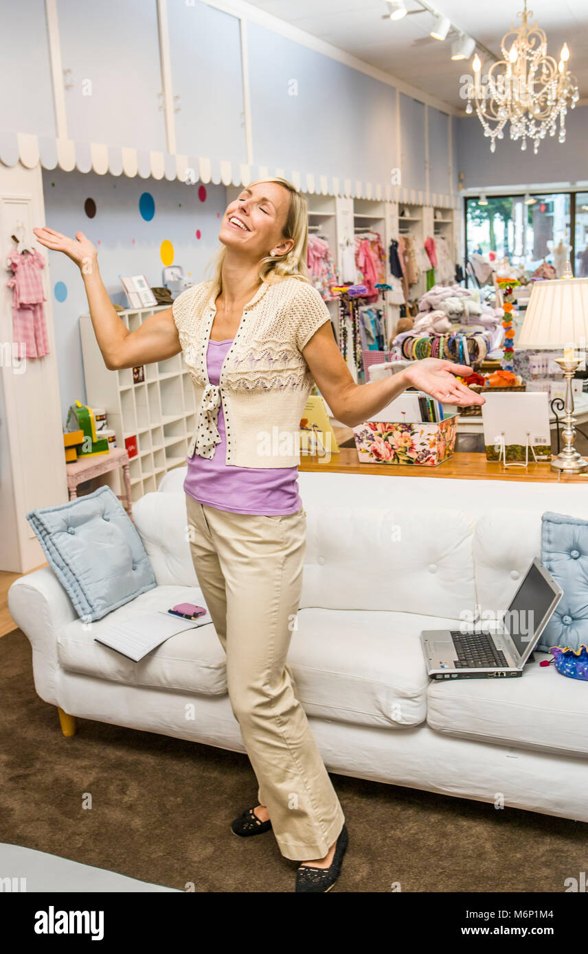A happy businesswoman in her store. - Stock Image