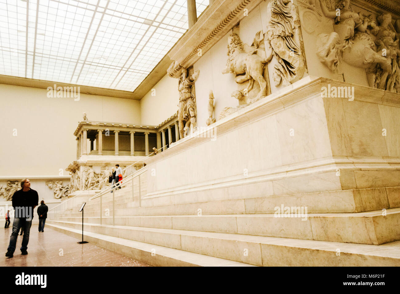 A visitor stands by the Pergamon Altar (2nd century BC) at the Pergamon Museum in the Museum Island, Berlin, Germany - Stock Image