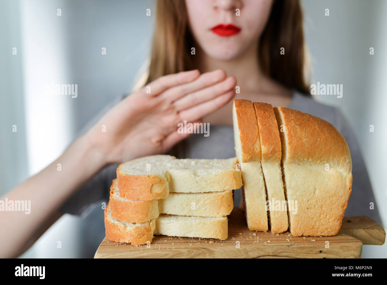 Gluten intolerance and diet concept. Young girl refuses to eat white bread. Shallow depth of field. Selective focus - Stock Image