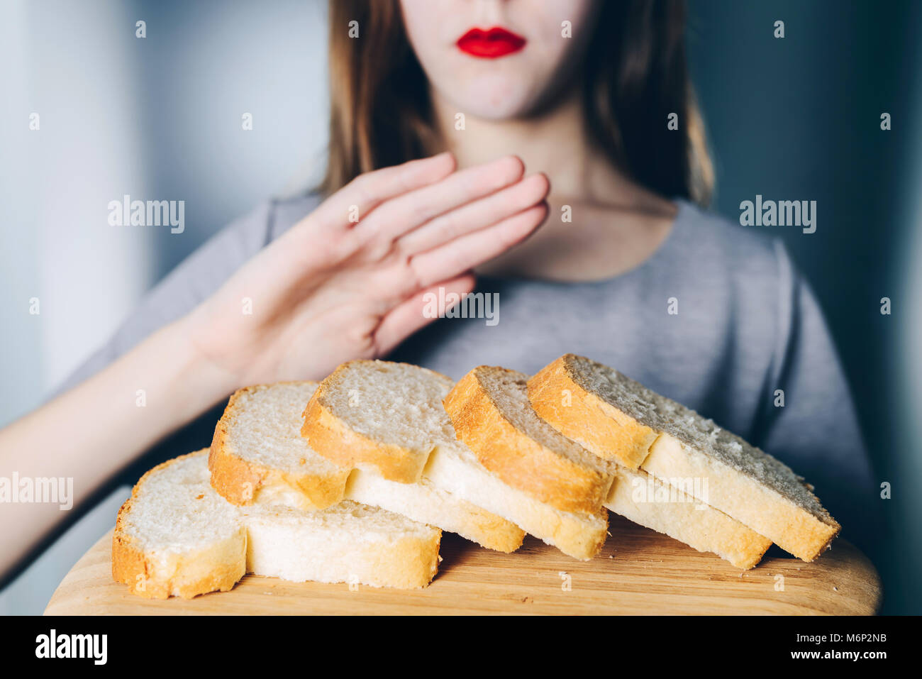 Gluten intolerance and diet concept. Young girl refuses to eat white bread - Stock Image