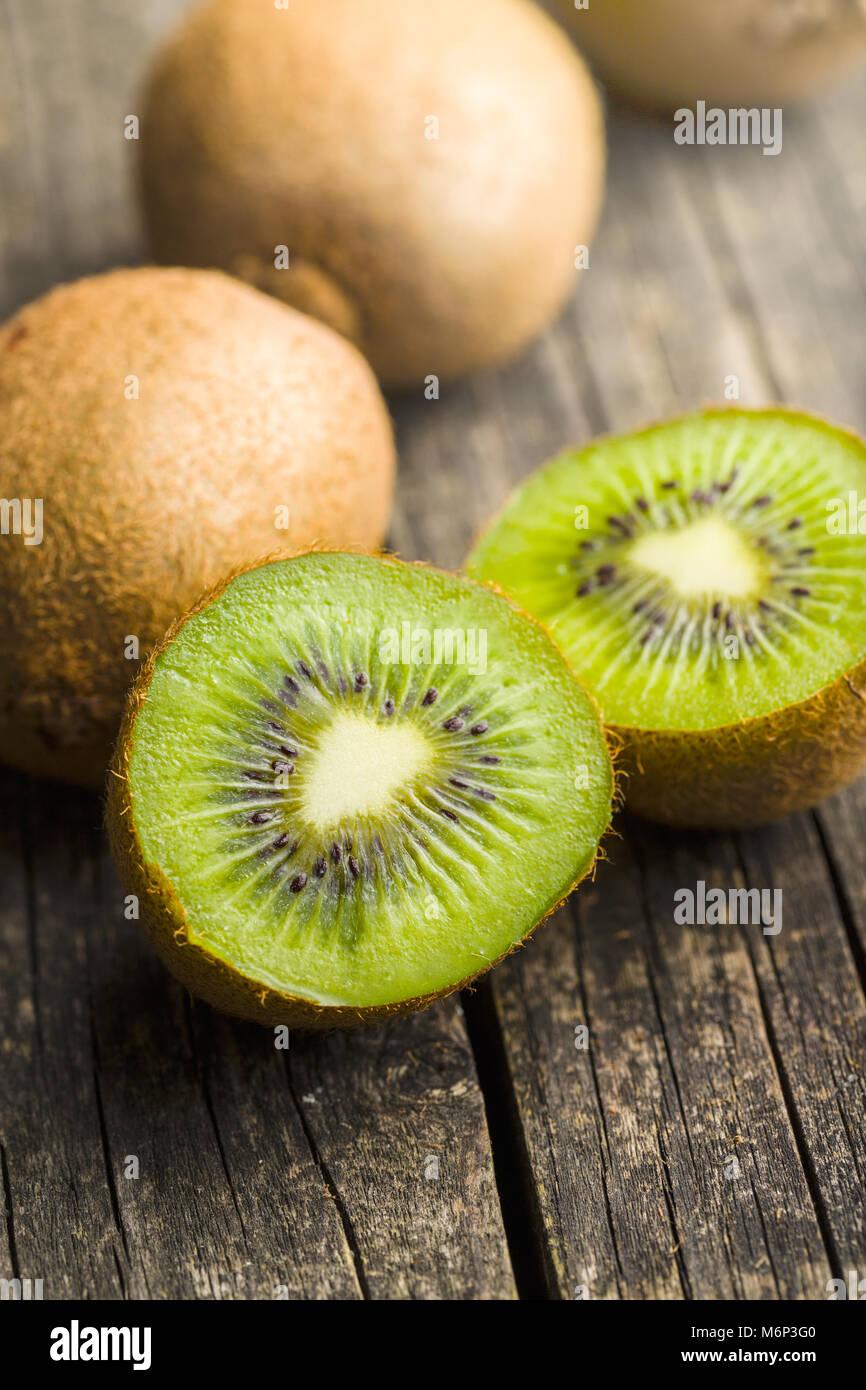 Halved kiwi fruit on wooden table. - Stock Image