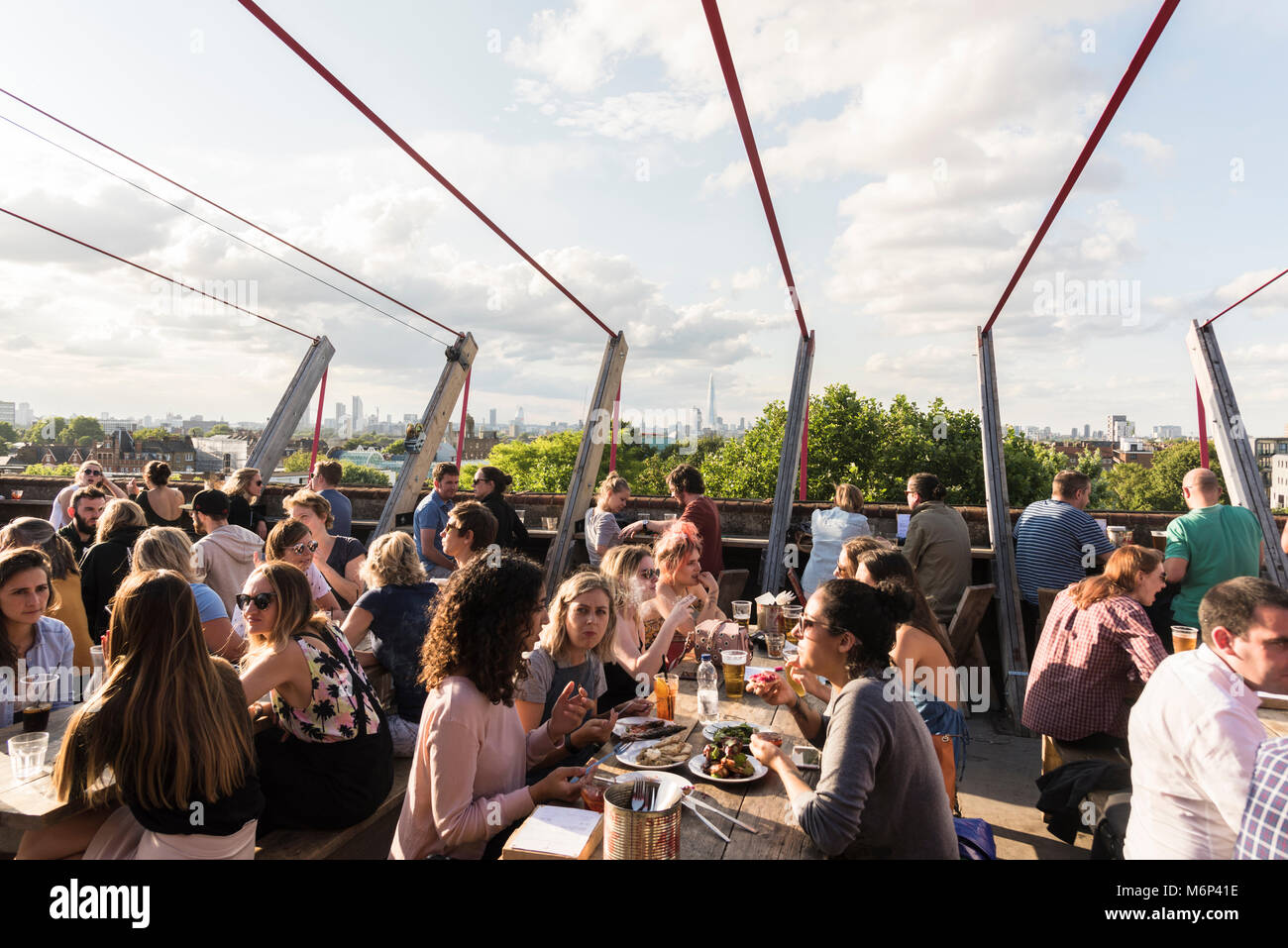 Young people socialising and enjoying a drink together at Franks Cafe outdoor rooftop bar and restaurant with view - Stock Image