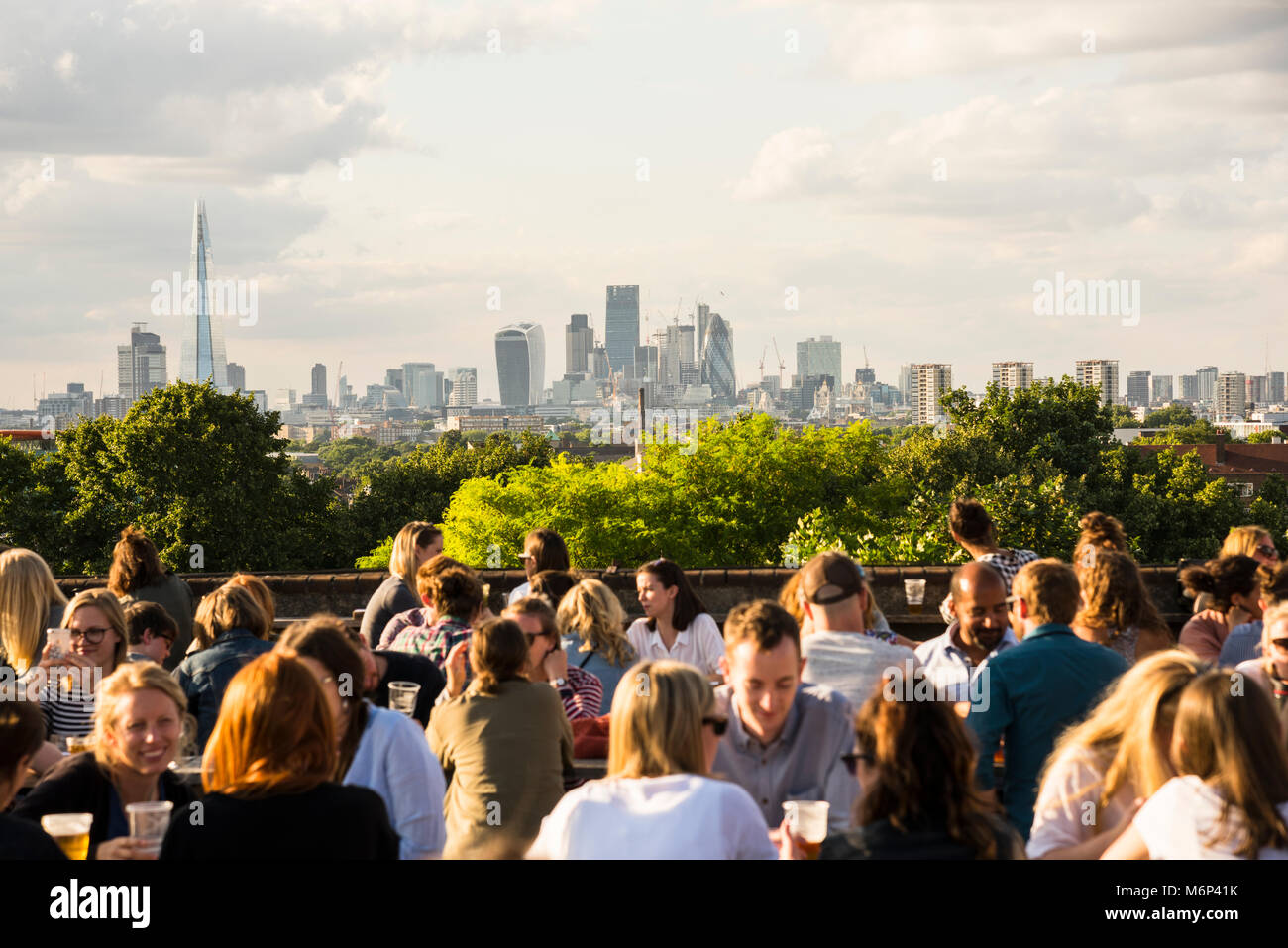 Young people socialising, enjoying a drink together at Franks Cafe outdoor rooftop bar and restaurant in Peckham, - Stock Image