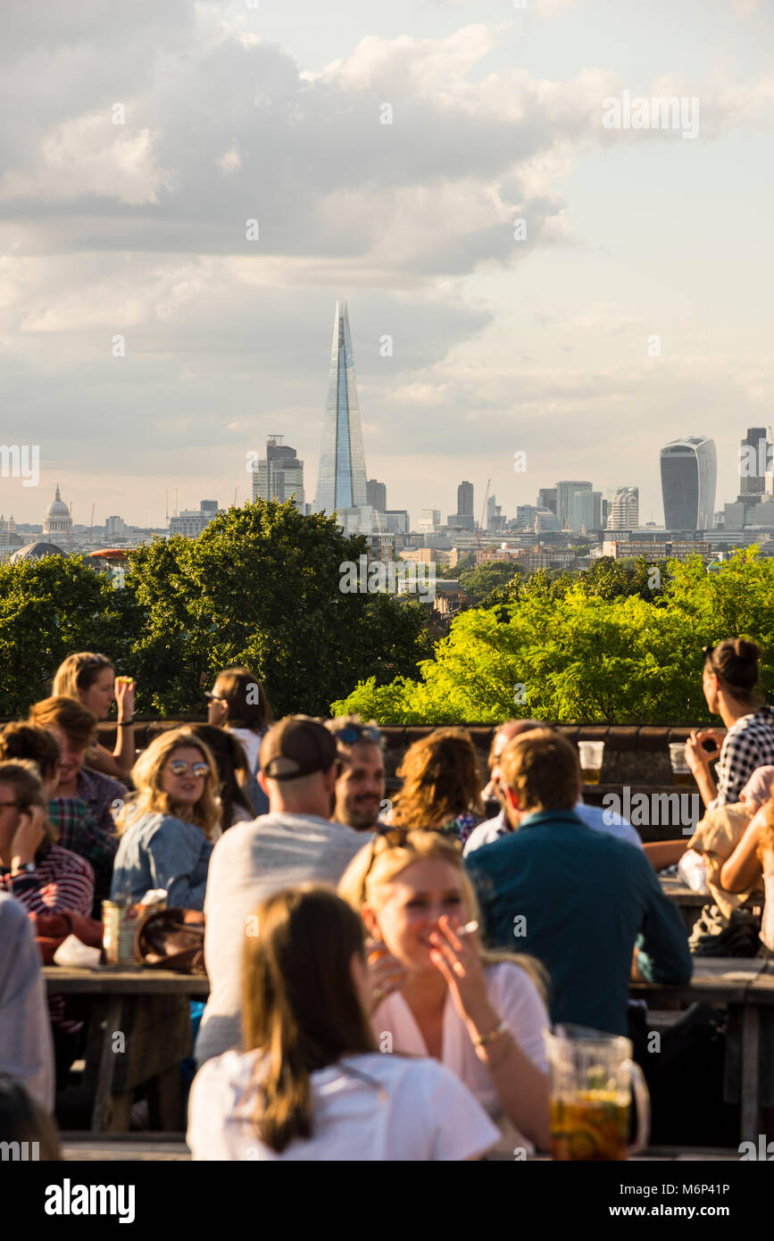 People socialising and enjoying a drink together at outdoor rooftop bar with view of the city. - Stock Image