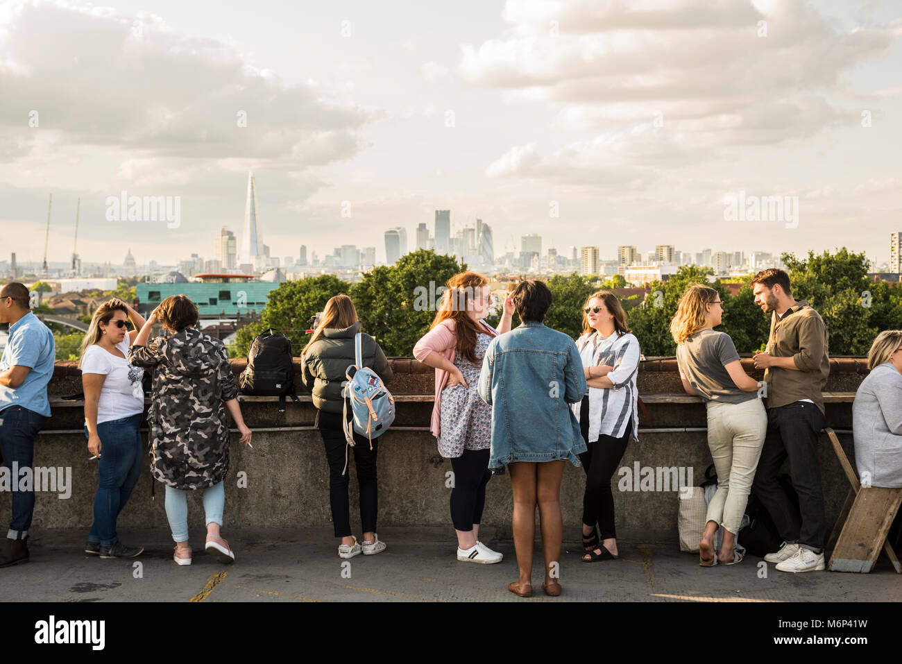 People socialising and enjoying a drink together at Franks Cafe outdoor rooftop bar with view of the city. - Stock Image