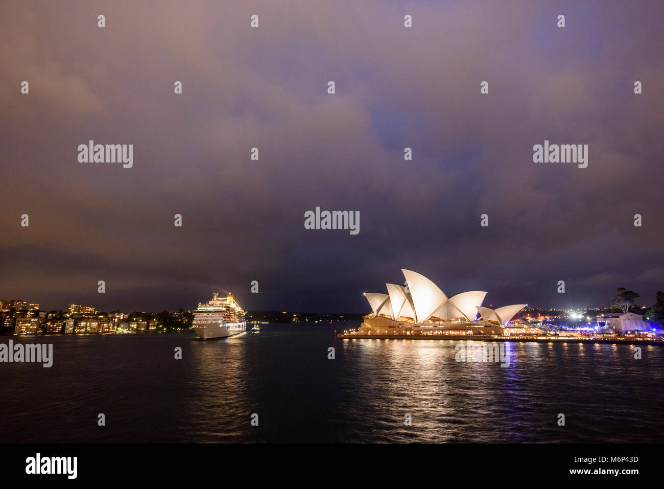 Sydney Harbour with illuminated cruise ship and Sydney Opera House at dusk under stormy sky. - Stock Image
