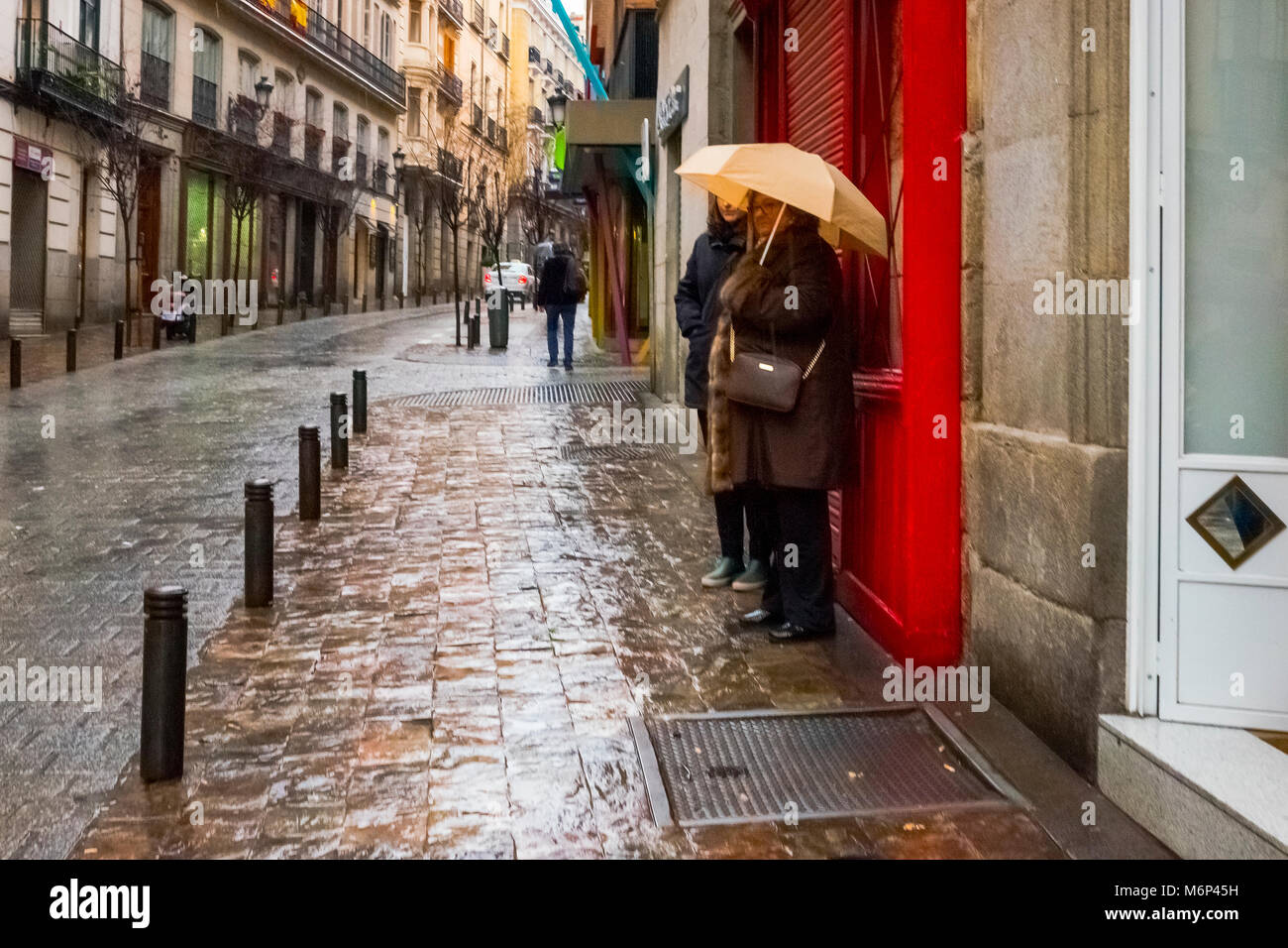 Two women carrying umbrellas sheltering from the rain in Madrid. - Stock Image