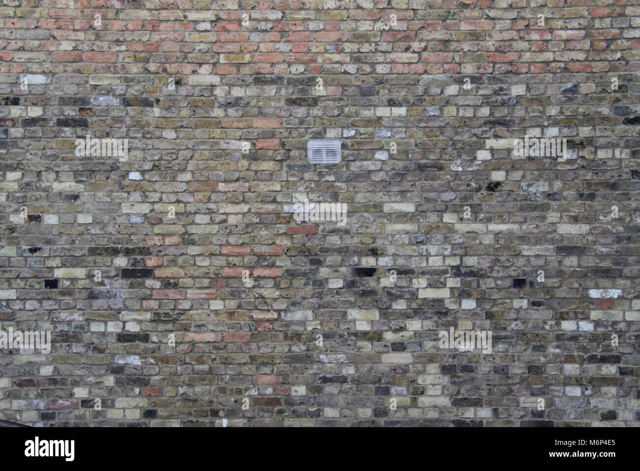 Brickwall background with T shape variance in brick type and small vent in middle, West London - Stock Image