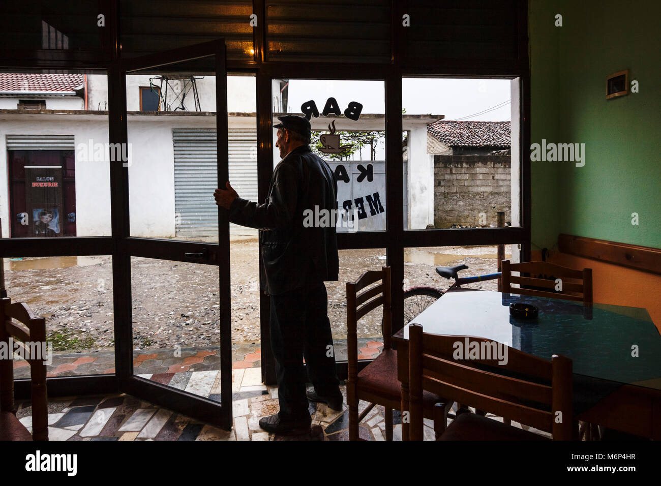 A man looking outside a coffehouse in Kiras, the 'quarter of the blood' where a wall has been built to protect - Stock Image