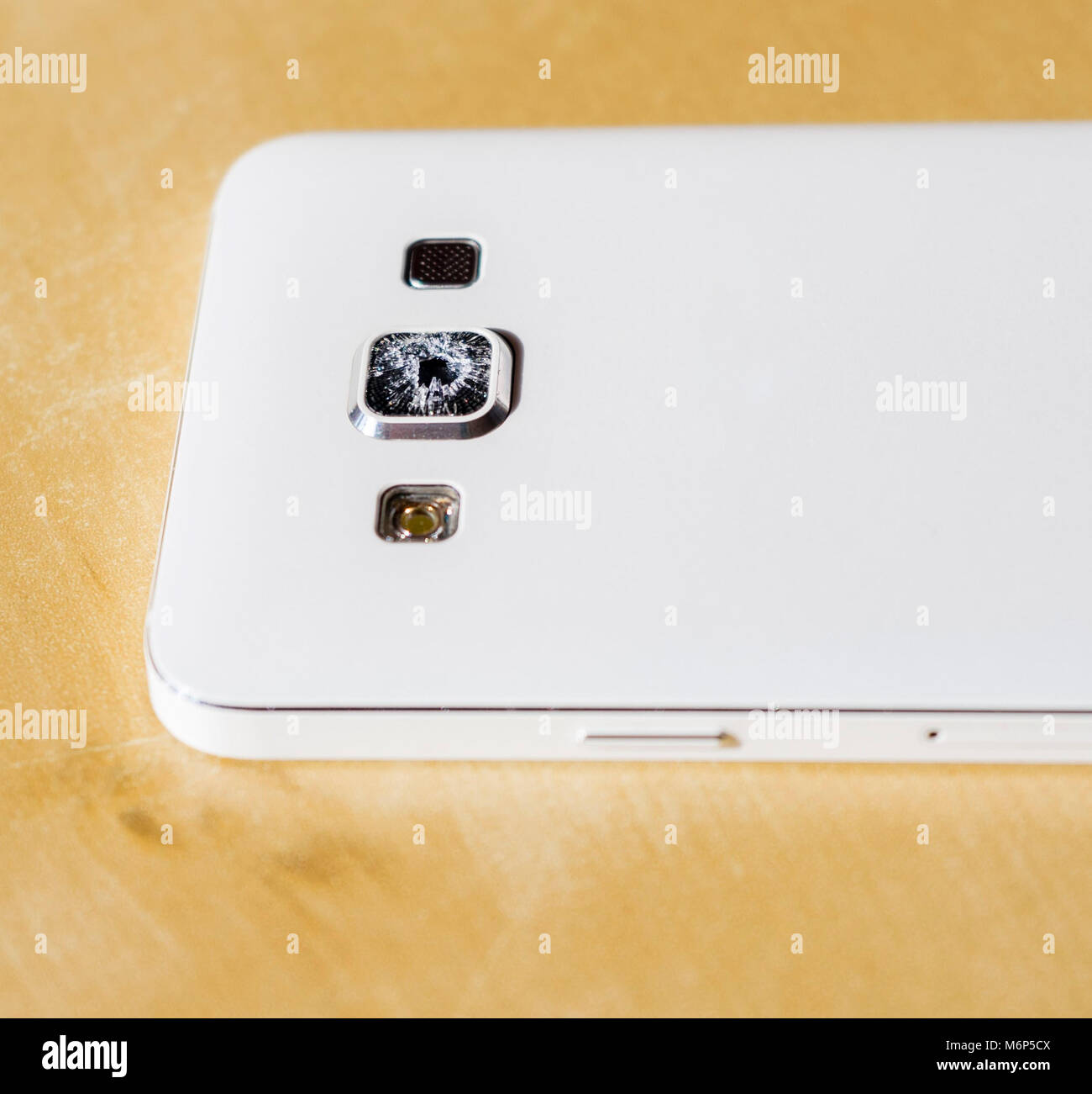 Close up of a white mobile phone with damaged/  cracked/ broken/ shattered protective camera lens glass - with copy - Stock Image
