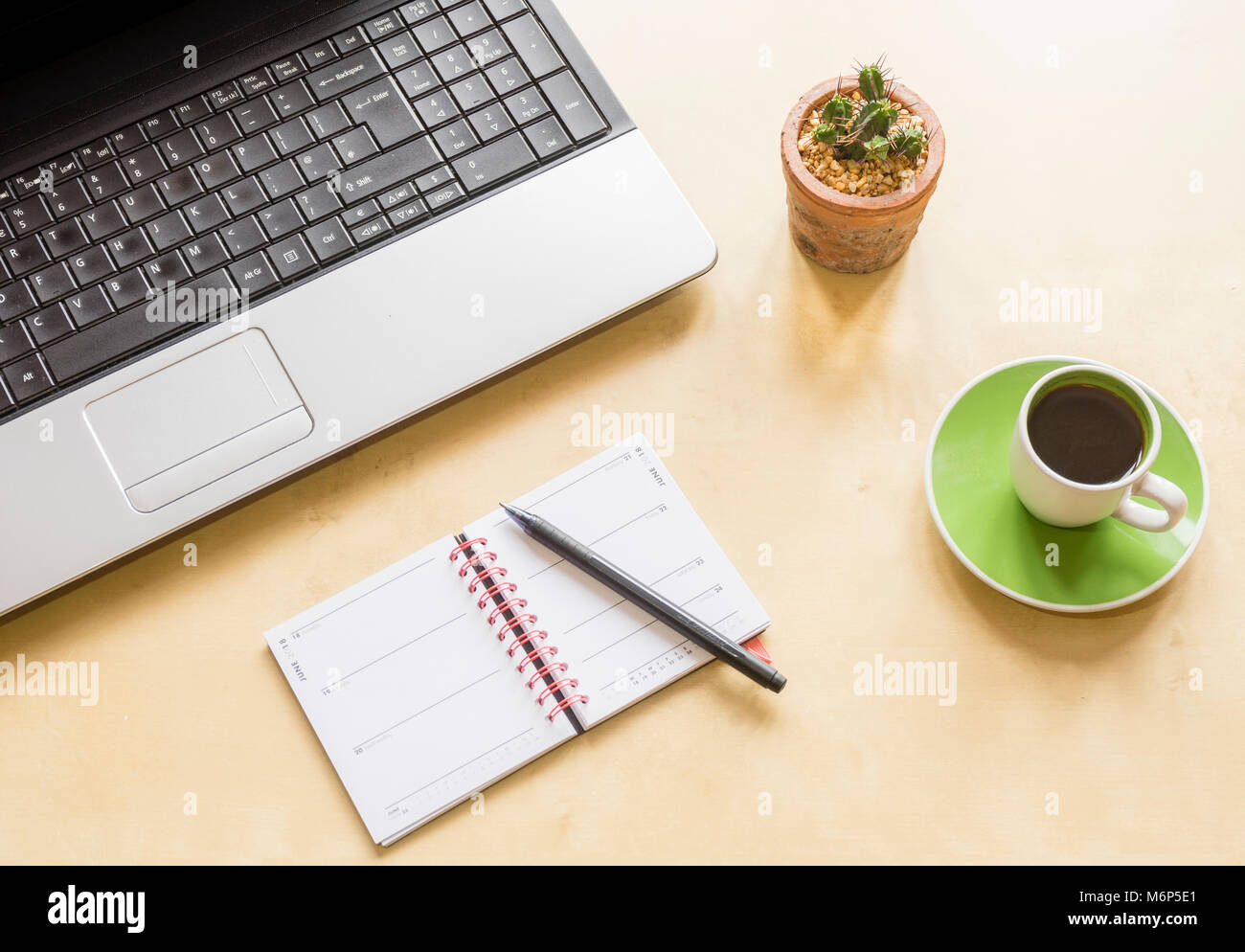 High-angle shot of a home office desk space with laptop, cactus plant, coffee cup and saucer and a calendar with Stock Photo