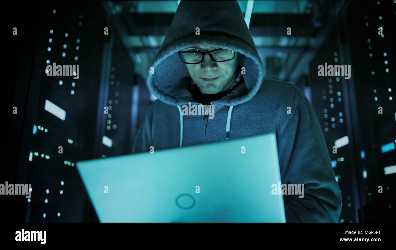 Low Angle Close-up Shot of Computer Hacker in Hoodie, Holding Laptop. He Breaked in a Corporate Data Center. - Stock Image