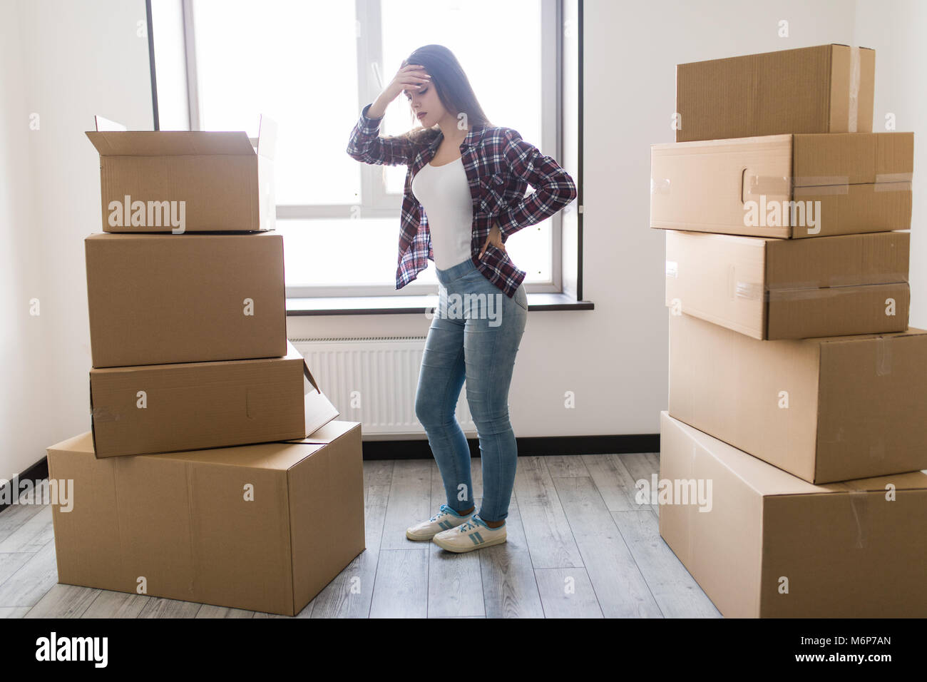 Young woman suffering from pain after moving heavy box - Stock Image