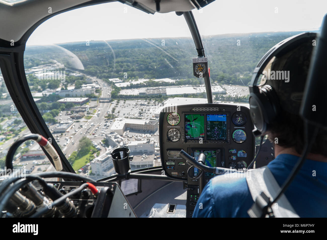 New York City, Circa 2017: Aerial view inside helicopter cockpit flying over suburban area highway traffic on a - Stock Image