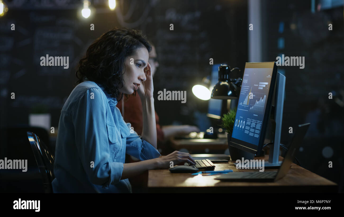 Stressed, Overworked Female Financier Holds Her Head in Hands while Working on a Personal Computer. In the Background - Stock Image