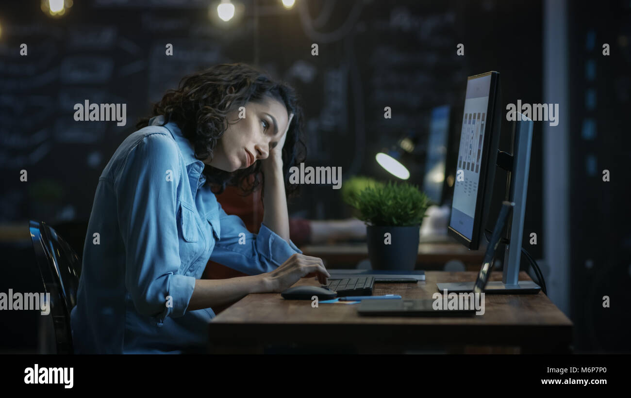 Tired, Overworked Female Financier Holds Her Head in Hands while Working on a Personal Computer. In the Background - Stock Image