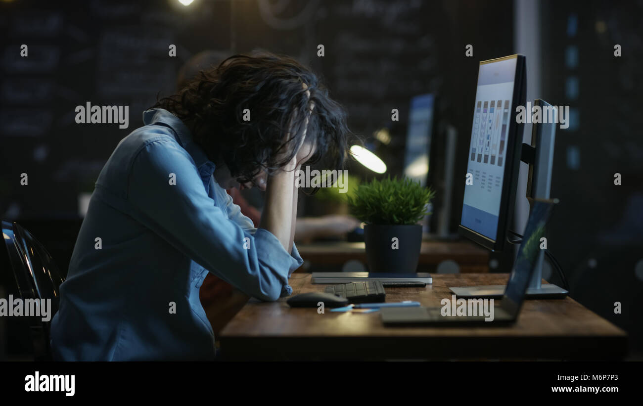 Tired, Overworked Female Mobile Phone App Designer Holds Her Head in Hands while Working on a Personal Computer. - Stock Image