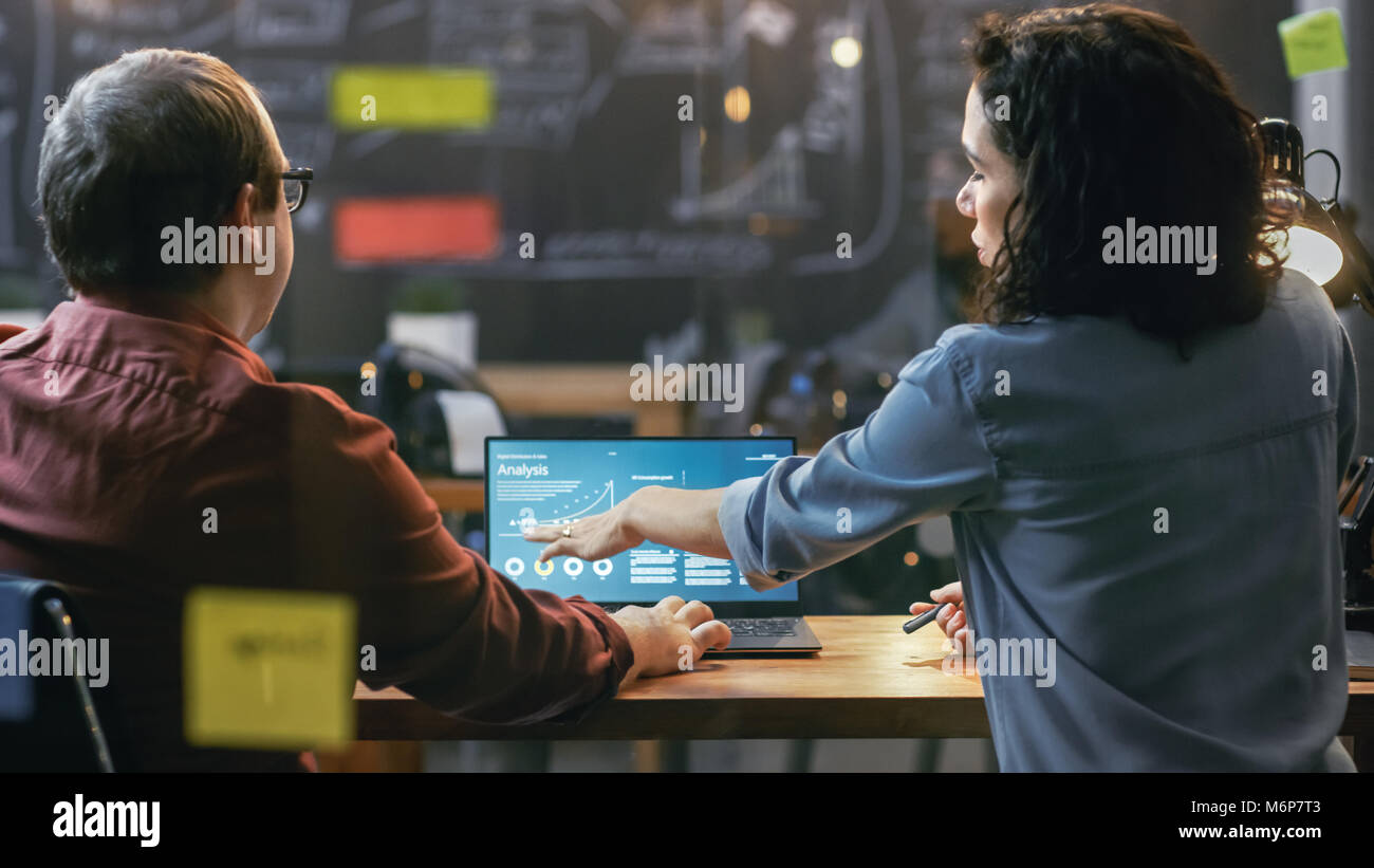 Male and Female Financiers Look at Statistics and Graphs Shown on the Laptop, They Talk Solving Problems. In the - Stock Image