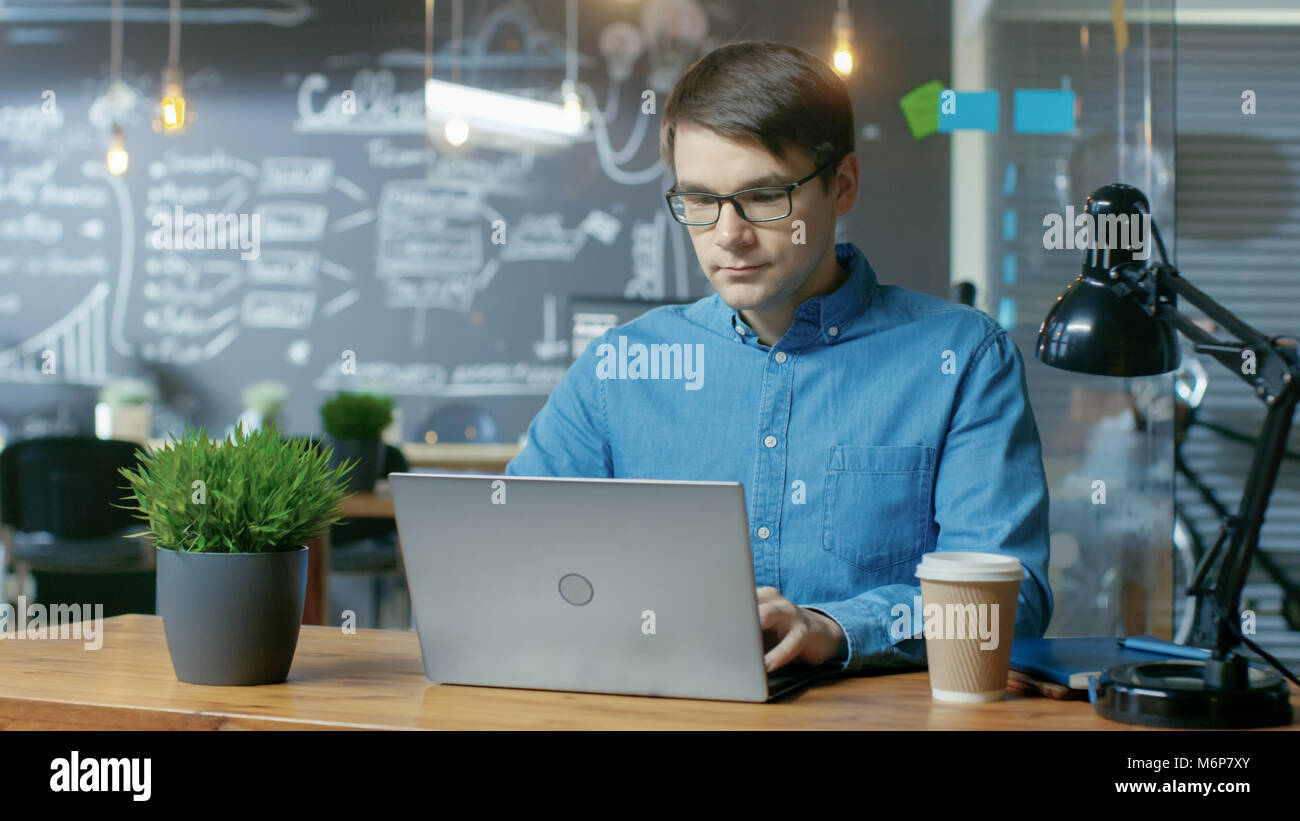 Handsome Young Office Employee Works on a Laptop Computer. He's Working in the Creative Stylish Office. Stock Photo