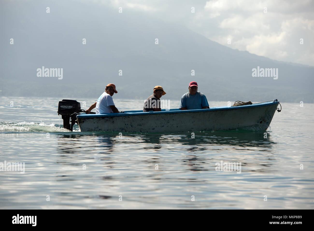 Indigenous, ethnic Maya men travelling by boat on Lake Atitlan. Lake Atitlán, Sololá Department, Guatemala. - Stock Image