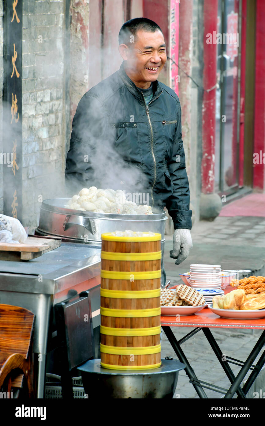 Outdoor kitchen with steaming dumplings and other street food, Pingyao, Shanxi Province, China - Stock Image