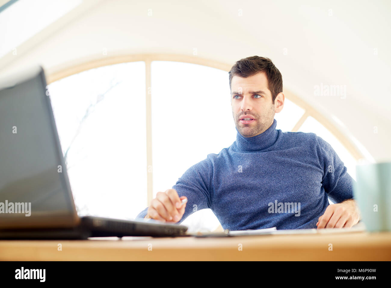 Portrait of casual young man wearing turtleneck sweater and looking thoughtul while working on laptop at home. Home - Stock Image