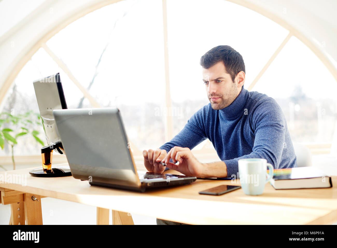 Portrait of young casual businessman using laptop while working at the office. - Stock Image