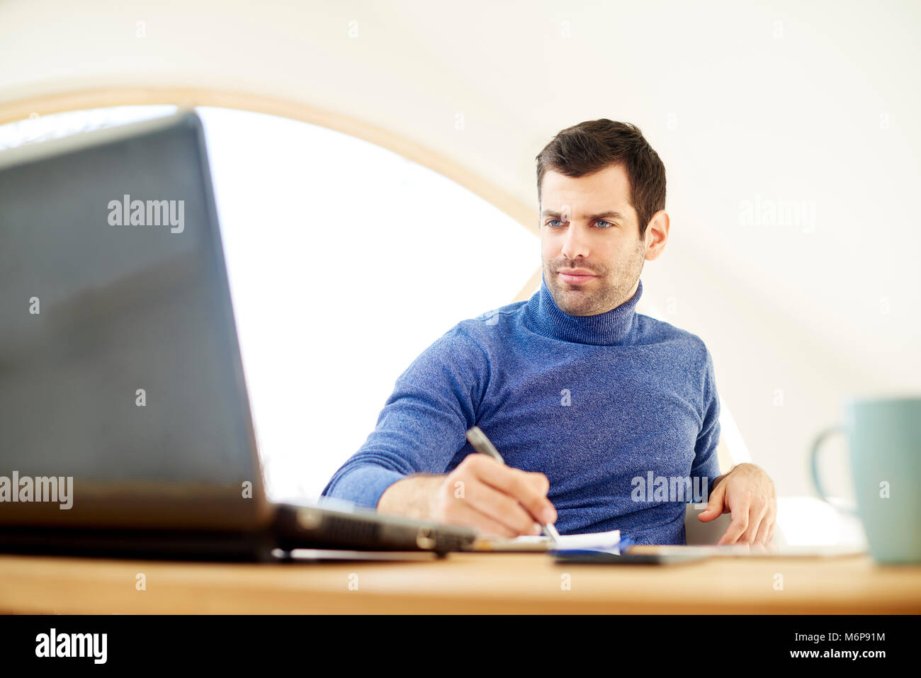 Portrait of casual young man wearing turtleneck sweater and looking thoughtul while working onl laptop and doing - Stock Image