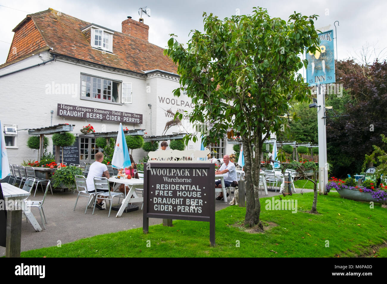 Woolpack Inn with people dining outside, a 16th century pub in Warehorne, Kent, UK - Stock Image