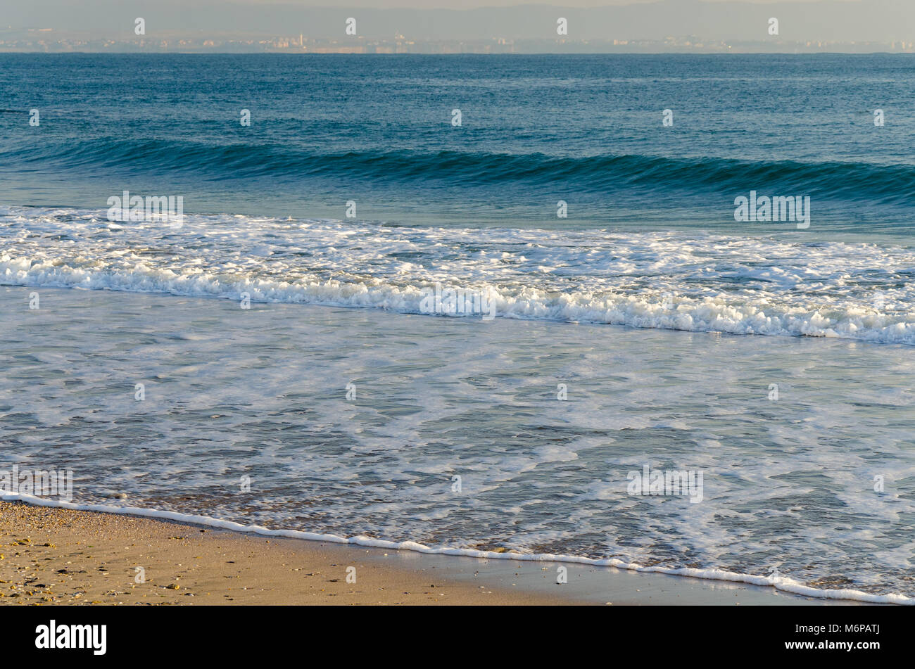 Seascape background with gentle blue waves lapping on the beach with yellow sand - Stock Image