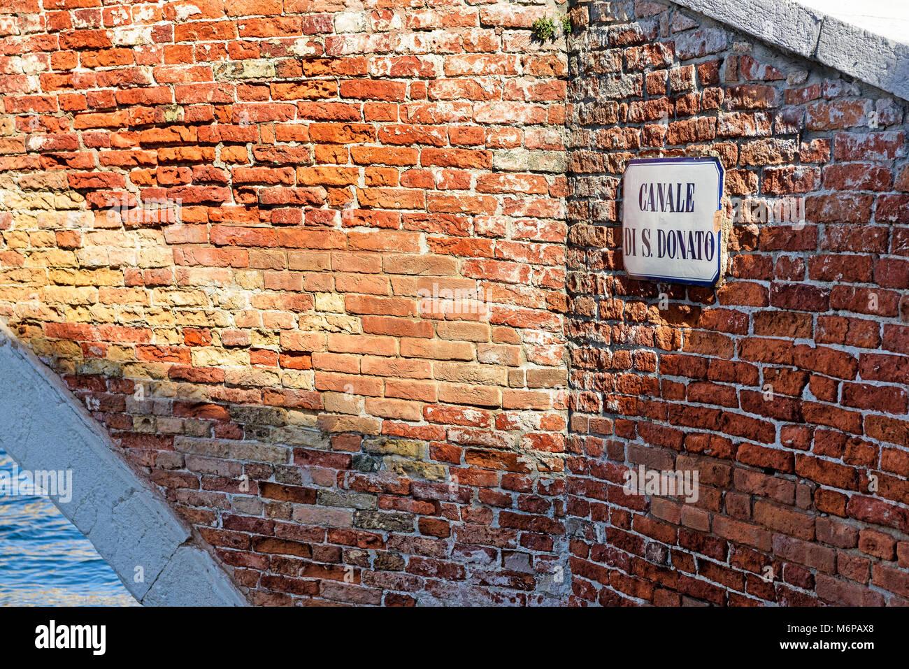 Canale di San Donato road name sign on red brick wall, Murano island, Venice, Italy - Stock Image