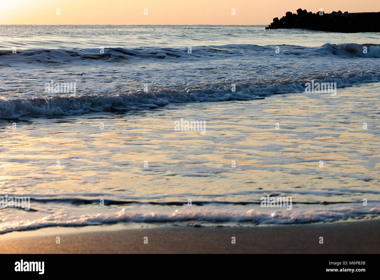 Brightly lit seascape background with golden colored gentle breaking sea waves lapping on the beach at sunrise - Stock Image