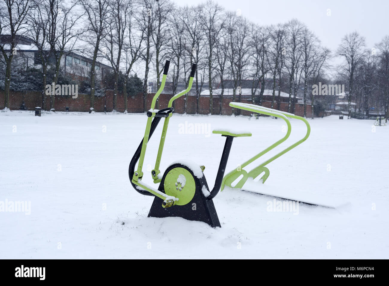 Exercise Equipment  in a public park covered in snow,UK. - Stock Image