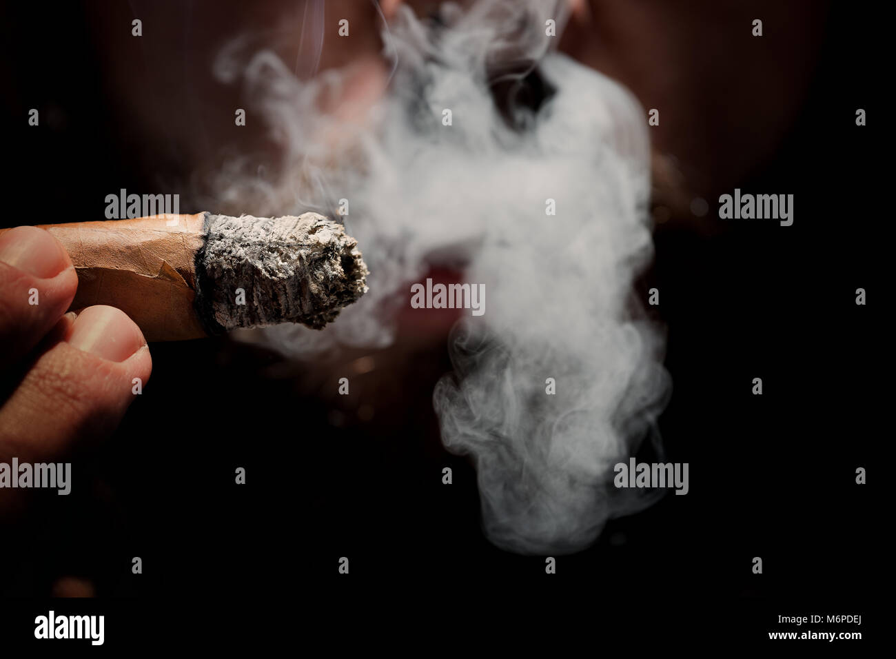 Close-up portraits of man smoking cigar, focussed on exhaling smoke, reduced light, cigar in focus - Stock Image