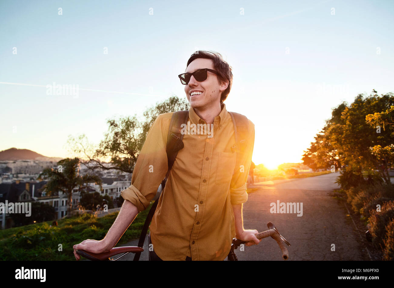 Young guy walking his bike through a park - Stock Image