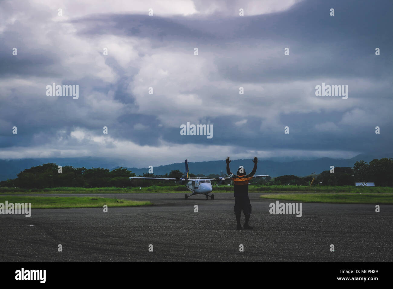 Air traffic control directing a Twin Otter into the arrival bay at Honiara airport - Stock Image
