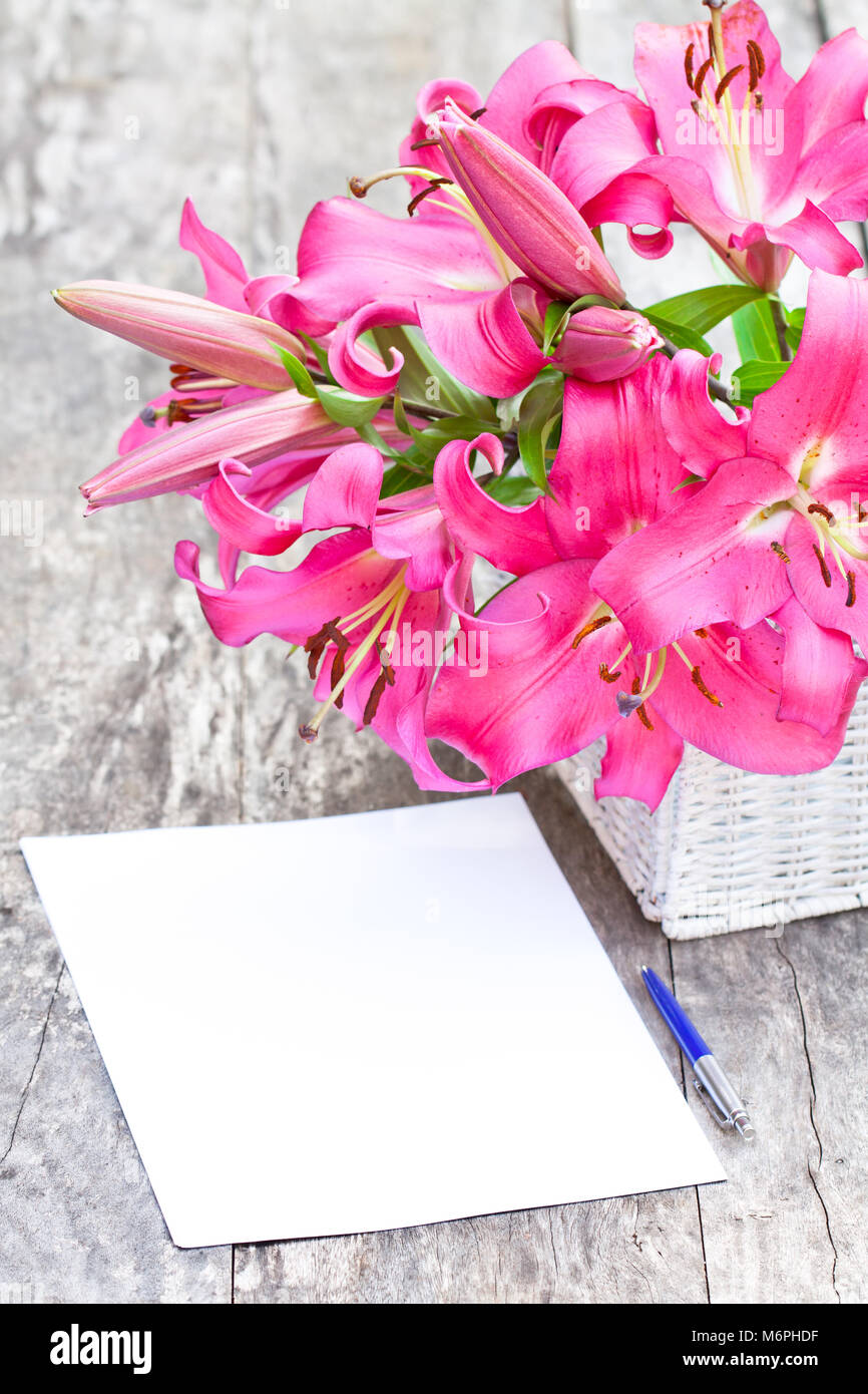 Pink lily flowers bouquet and blank paper sheet with pen on rustic ...