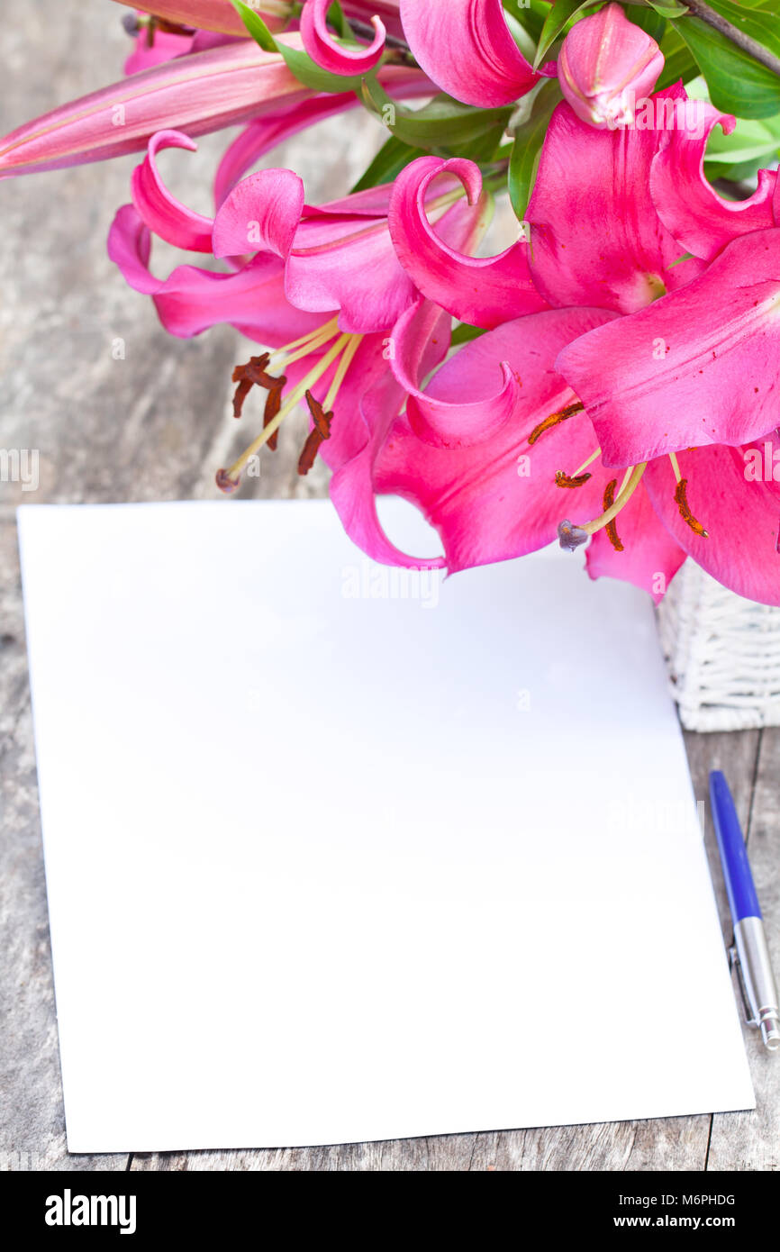 Pink lily Robina flowers bouquet and blank paper sheet with pen on ...