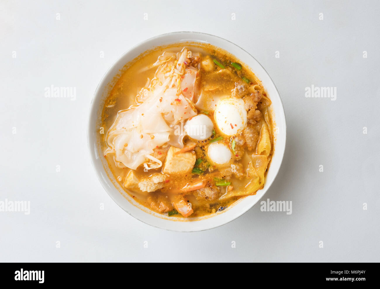 Top view of spicy TOM YAM pork noodles soup isolated on