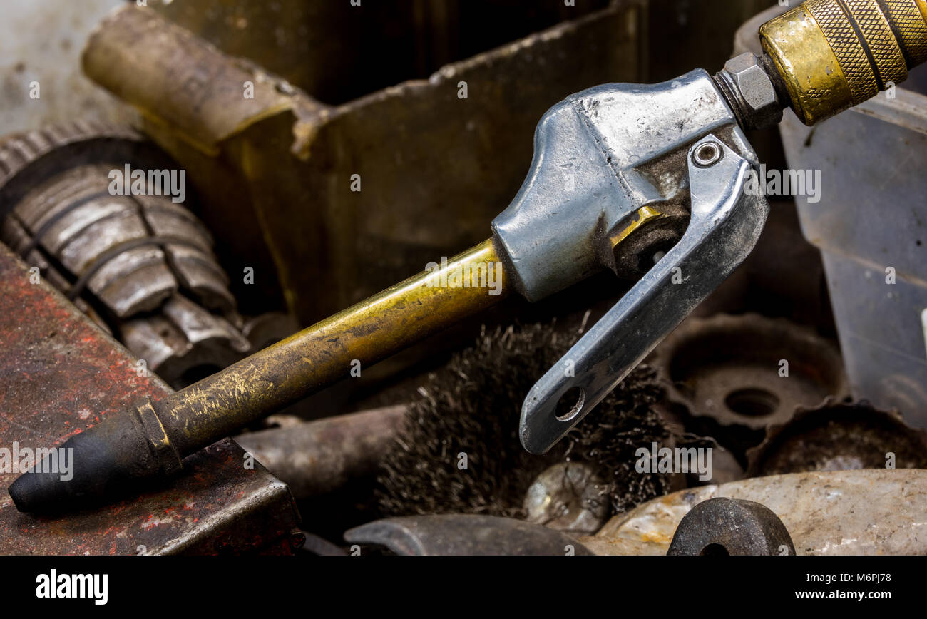 Vintage antique automotive machine shop air compressor hose nozzle with a brass neck and rubber tip in a drawer - Stock Image