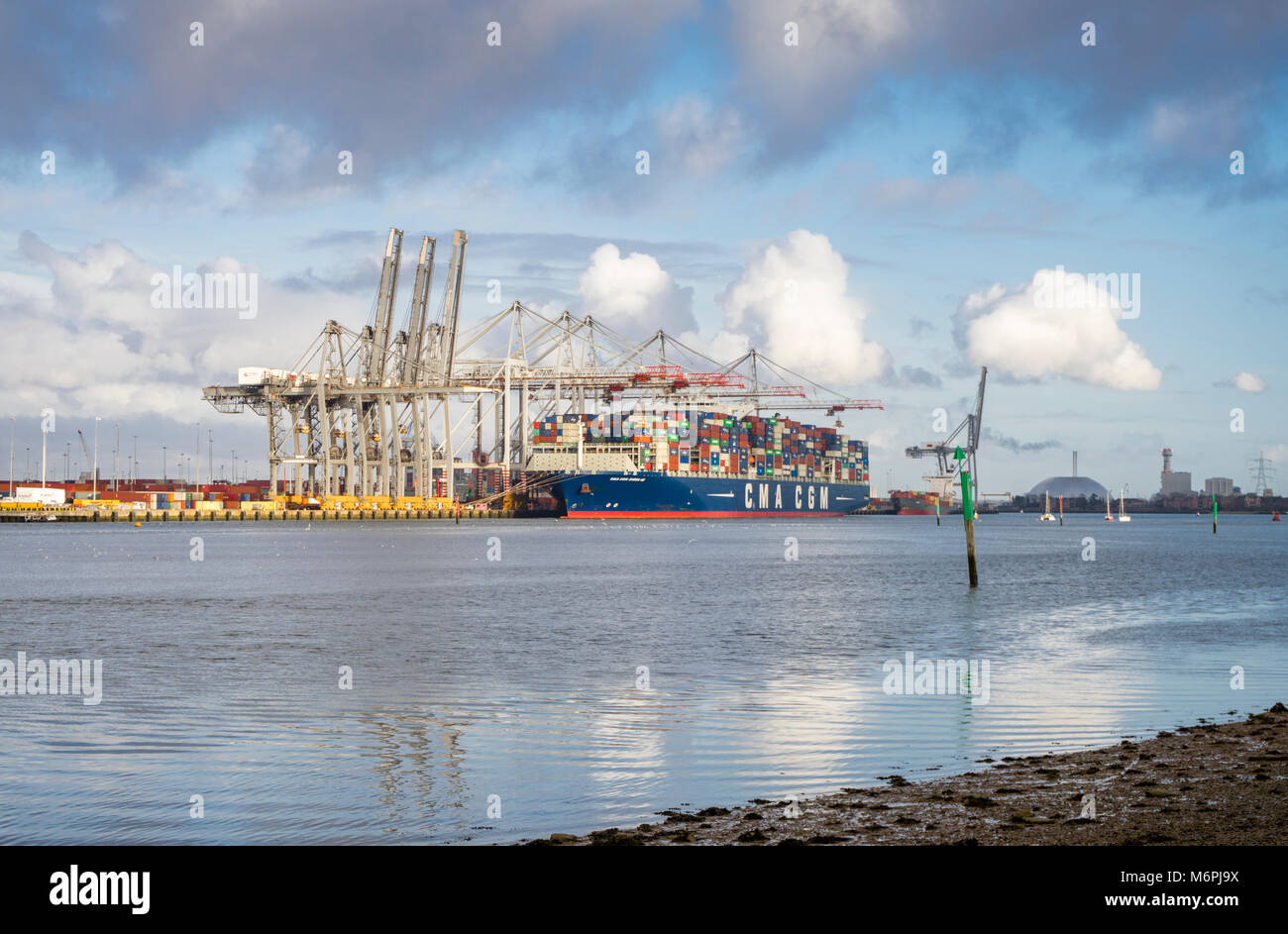 View over the River Test to Southampton port/ docks with a container/ cargo ship being unloaded/offloaded in March - Stock Image