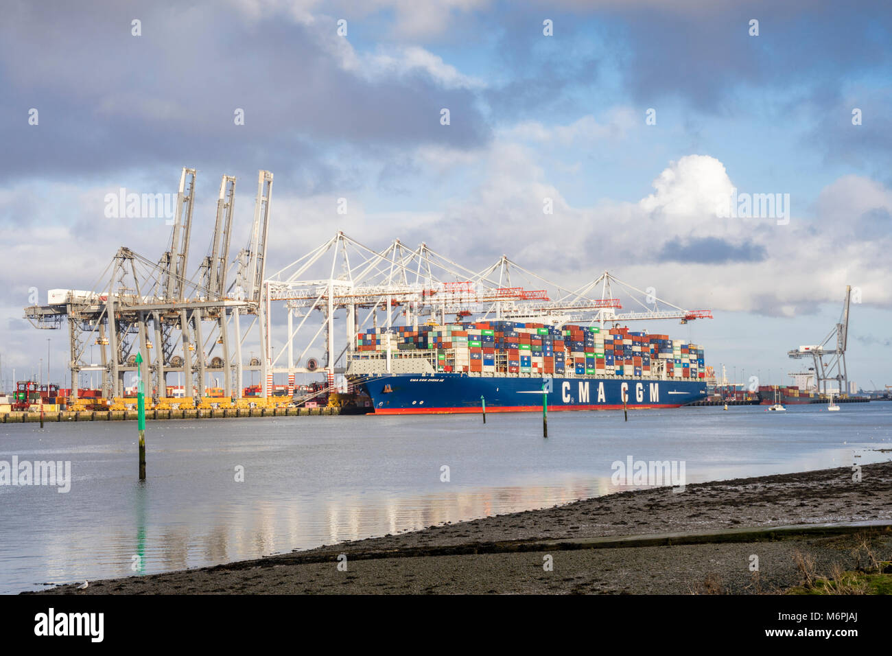 View over the River Test to Southampton port/ docks with a container/ cargo ship being unloaded/offloaded in 2018, - Stock Image