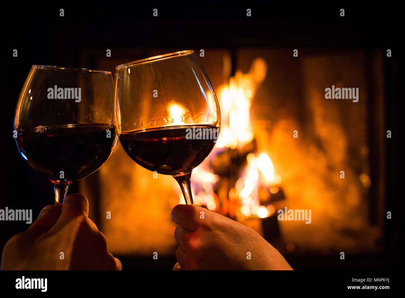 Couple holding pair of glasses with wine at fire pit close up Stock Photo