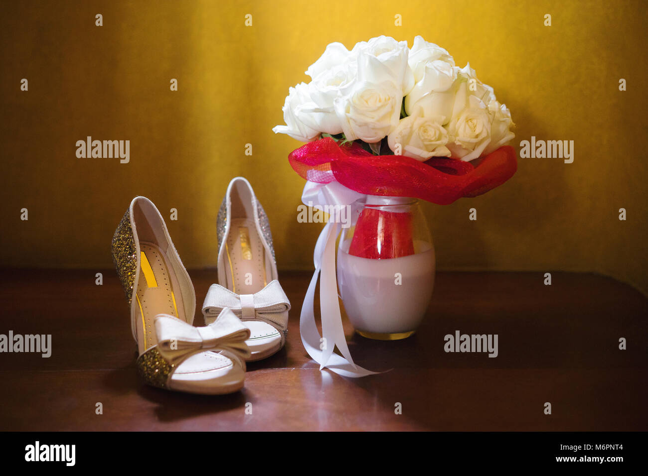 The bouquet of the bride with cream roses and the bride's shoes, on the wooden floor wth yellow background, the Stock Photo