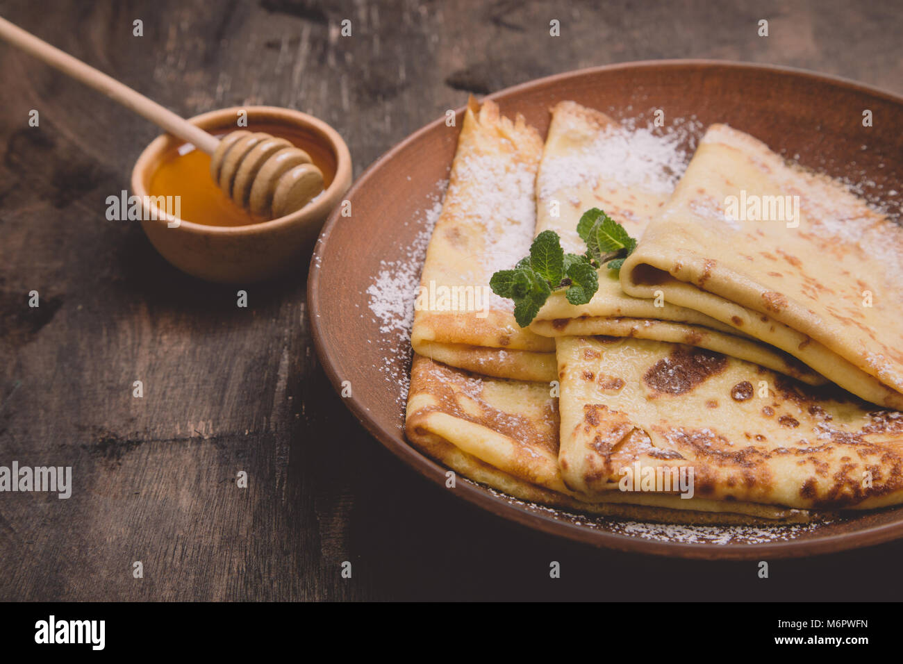 fresh pancakes with fragrant maple syrup and honey. Russian holiday pancake week. crepes with honey or syrup. - Stock Image