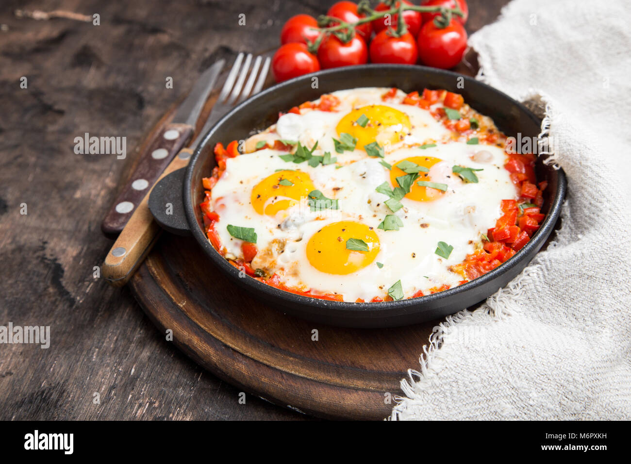 Tasty and Healthy Shakshuka in a Frying Pan. Fried eggs with tomatoes, bell pepper, vegetables and herbs. Middle - Stock Image