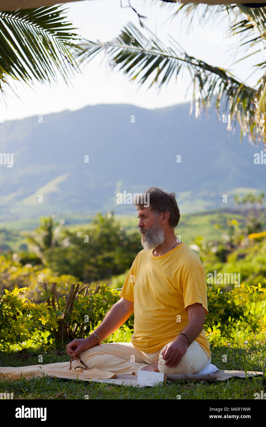 A man with beard sitting on yoga mat and practising meditation with mala beads in nature. Attending retreat in Fiji. - Stock Image