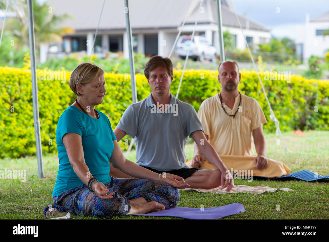 People sitting on their yoga mats outside in nature practising meditation with crossed legs. Attending retreat in - Stock Image