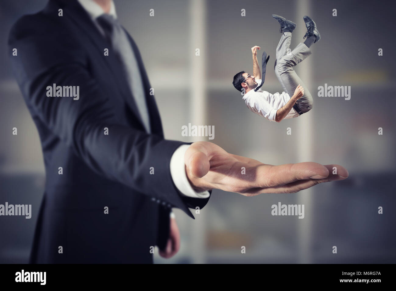 Businessman is saved from a big hand. Concept of business support and assistance - Stock Image